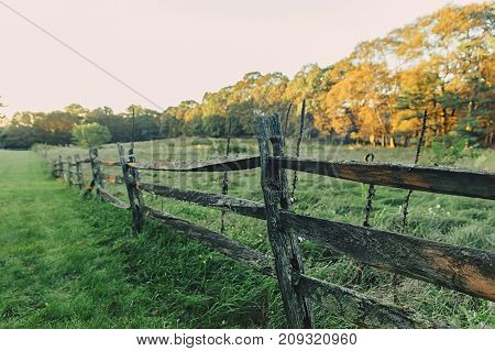old wooden fence on the background of autumn rural landscape. farm scene. Copy space for your text