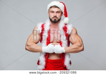 Sexy Santa Claus . Young muscular man wearing Santa Claus hat demonstrate his muscles. Muscular Fighter kickbox With white Bandages. Christmas