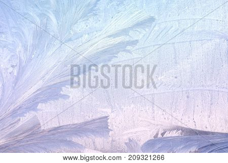 Ice patterns on winter glass. Christmas frozen background. Winter toning effect
