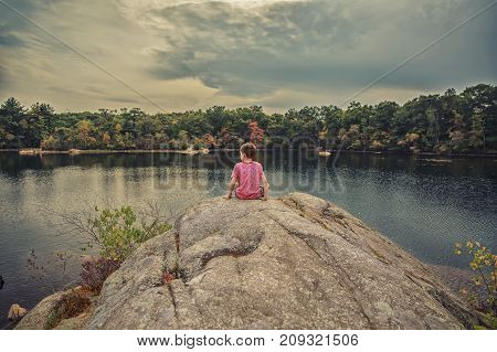 boy on the lake admires the foliage. child sits on a large boulder in the middle of an autumn lake