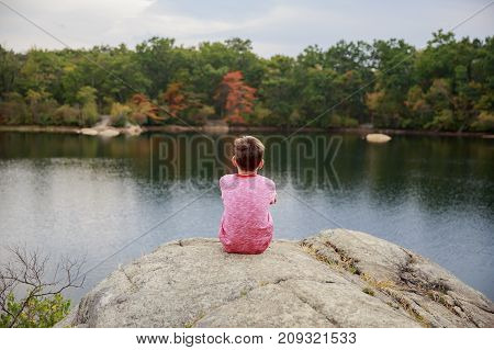 child sits on a large boulder in the middle of an autumn lake. boy admires the foliage