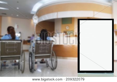 blank advertising billboard or showcase light box with copy space for your text message or media and content with blurred image of patients in wheelchair waiting in lobby at hospital background