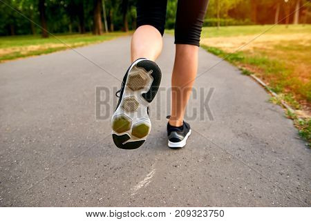 Close up from the back of a young blonde woman running away from the camera on the road in a park