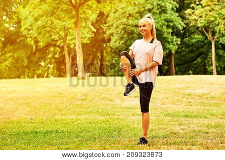 A beautiful young blonde woman stretching on the field in a park