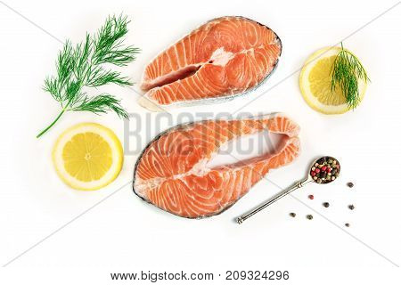 An overhead photo of raw salmon steaks with dill, lemons, and peppercorns, shot from above on a white background with a place for text