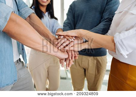 Great team. Friendly colleagues standing in circle and touching hands while making pyramid
