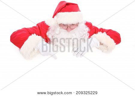 Kind Santa Claus looking out from behind the blank sign isolated on white background with copy space.