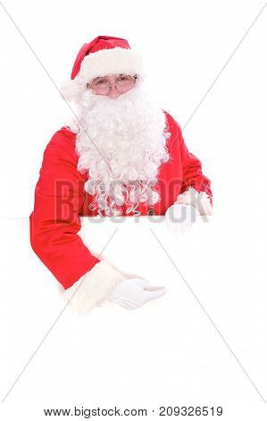 Kind Santa Claus pointing in white blank sign, isolated on white background.