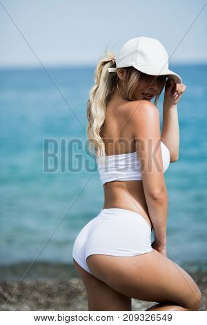 Beautiful young woman with long blond hair in white shorts is standing a back on the coastline of the sea.