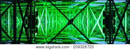 A metal structure glowing green in the darkness.