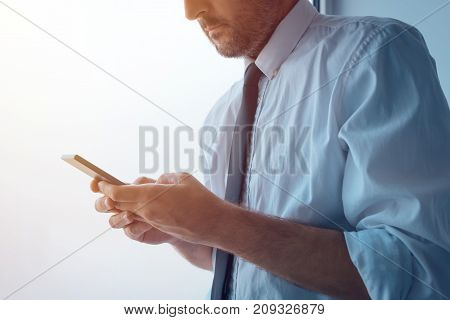 Businessman standing next to office window and texting. Adult caucasian business person in white shirt with tucked rolled up sleeves using mobile phone to send sms message.
