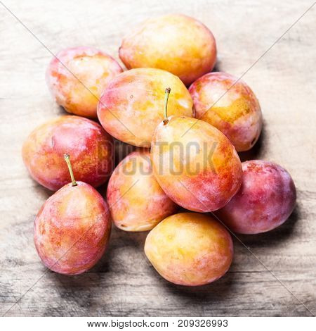 Fresh plumps on rustic wooden table with copyspace. Heap of beautiful plums