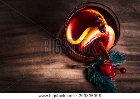 Christmas Hot mulled wine for winter with spices and orange slices on rustic table with copy space. Red Hot wine or gluhwein with Christmas Decorations on wooden background close up