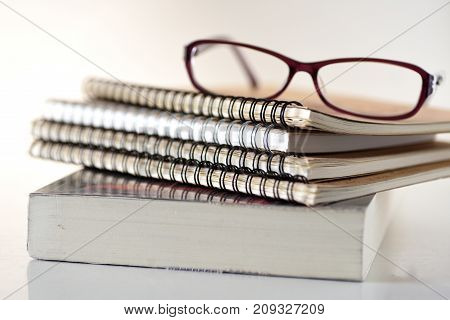 Stack of books, notebooks and glasses on white background