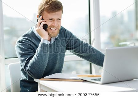 Leisure time. Attractive man keeping smile on his face and holding telephone while looking at screen of his computer