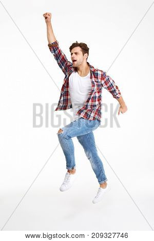 Full length portrait of a casual attractive man jumping with hand outstretched isolated over white background