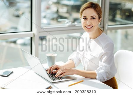 Look at me. Happy blonde keeping smile on her face and looking straight at camera while holding fingers on keyboard
