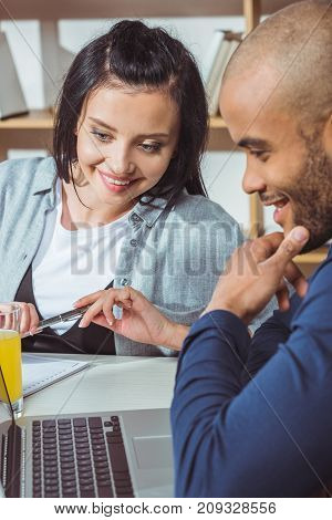 smiling young multiethnic couple using laptop together