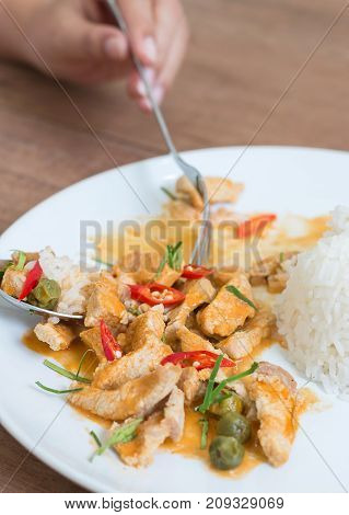 Red pork curry (Panang) with rice in white plate on wooden background Thai food