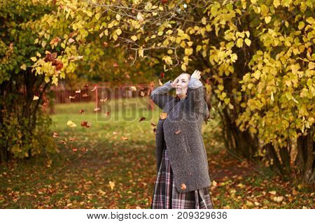 Girl In The Park Throws Autumn Leaves