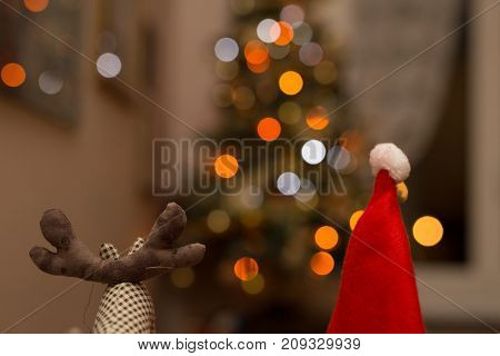 Rudolf and Santa Claus under  snow with lights in the background