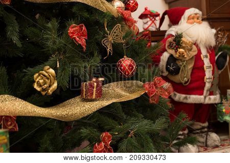 close up christmas tree with santa claus in the background