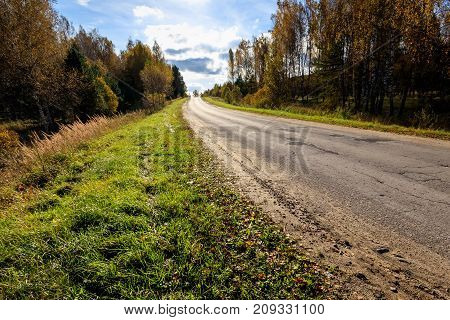 A Rural Road In An Autumn Sunny Day.