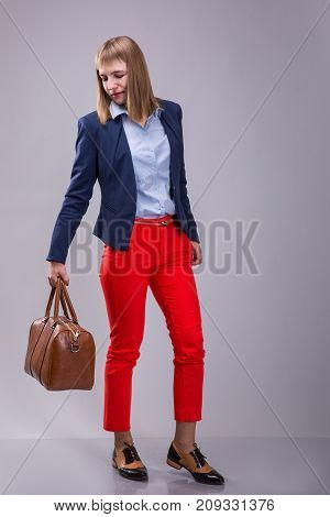 Fashion look of woman dressed red pants blue jacket brown bag over grey background. model looks at a leather bag