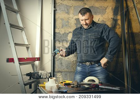 A working man performs finishing work in the house. Repair of an apartment living quarters.