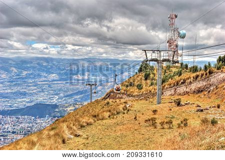 The Teleferico (touristic attraction) with it's cable cars going up and down the Pichincha mountain slopes, with the city of Quito in the background, Ecuador.