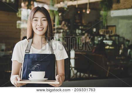 Barista asian women hands holding fresh coffee or latte art in white cup at coffee shop. Service Concept