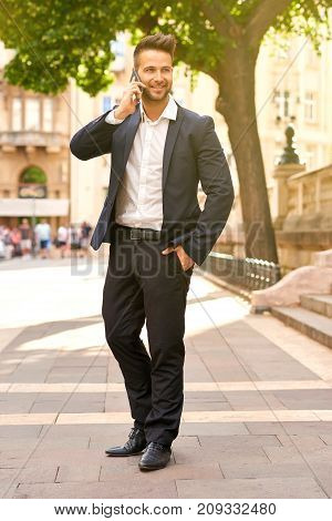 A handsome young businessman walking on the sunny street in a suit while talking on his smartphone