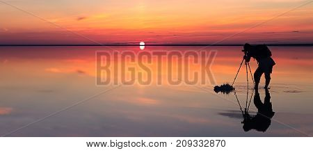 Silhouette of alone man takes a picture of a vibrant sunset reflected in shallow waters of solt lake. Banner size. The photographer takes a picture of the sunset