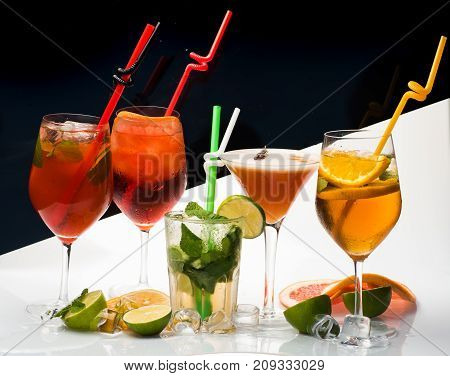 Cocktails on black and white background with mojito. Alcoholic beverage and fruit at restaurant. Party and summer vacation. Fruit slice and cocktail glass at bar. Drink and food.