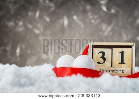 New Year Date On Calendar. 31st Of December. Empty copy space for inscription. New year concept. Wooden calendar set on the 31 of December with holiday balls and red ribbon on snow on grey background.