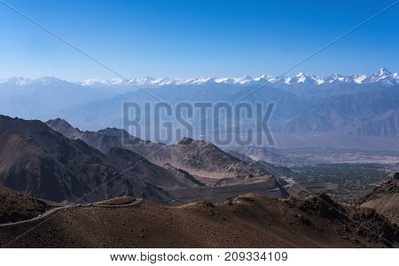 Landscape image of mountains and cars on the road in Ladakh with blue sky background India