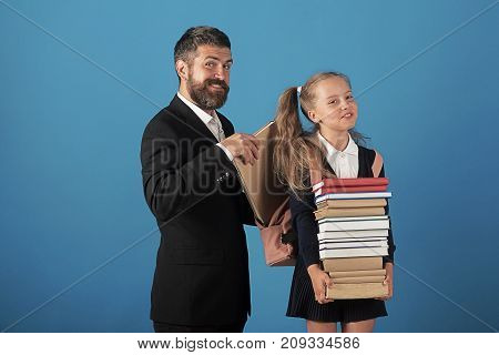 Girl and man in suit and school uniform. Kid holds pile of books and dad puts book into bag. Father and schoolgirl with tricky faces on blue background. Family life and alternative education concept