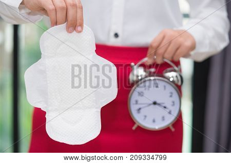 Woman holding alarm clock and sanitary napkin with red skirt - woman on her period