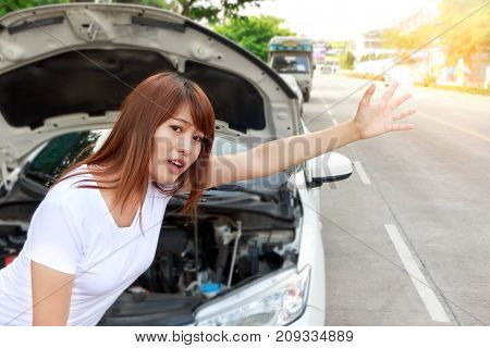 Woman looking for help after a car breakdown standing besides car and hitching a ride.