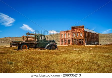 BODIE, CALIFORNIA, USA - MAY 22, 2016 : Car wreck and old buildings in Bodie ghost town, California. Bodie is a historic state park from a gold rush era  in the Bodie Hills east of the Sierra Nevada