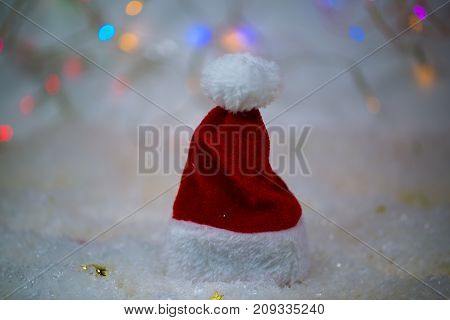 Santa Claus hat in the snow glittering background with stars