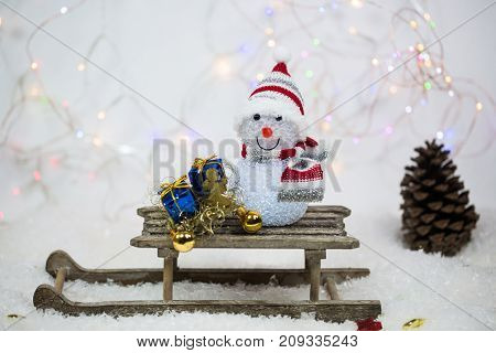 Snowman on sled glittering background, snow, present
