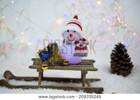 Snowman on sled glittering background, studio, still