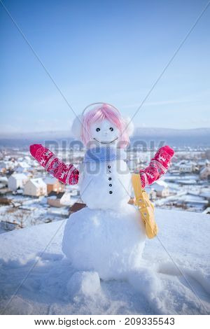 New year snowman from white snow with bag. Christmas or xmas decoration. Snowman in pink wig mittens and scarf. Happy holiday and celebration. Winter activity and party.