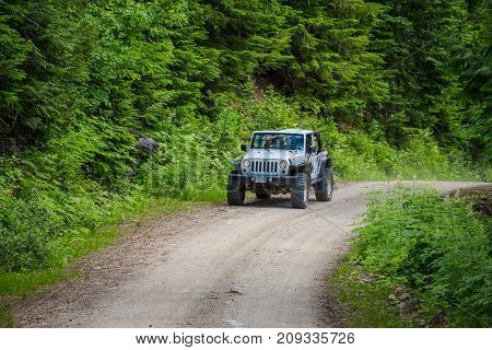 BLUE RIVER, CANADA - JUNE 30, 2017 : Tourists in a jeap on a safari tour in canadian Rocky Mountains.