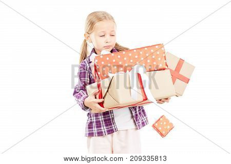 Studio portrait of little girl holding stack of Christmas gifts