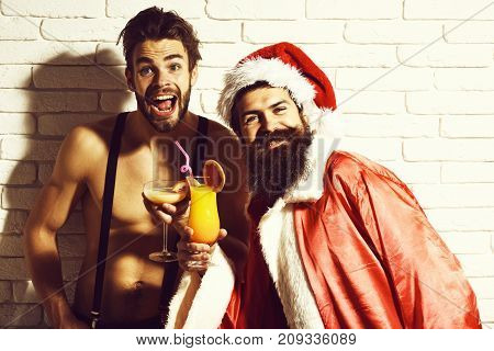 young handsome bearded santa with stylish long beard in red xmas hat and coat and sexy macho man with muscle torso on athletic body holding glass of alcoholic cocktails on brick wall background