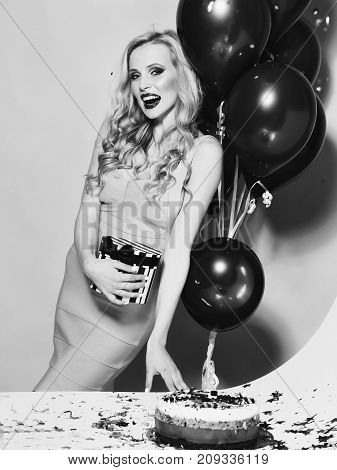 One pretty emotional young happy blonde girl with long curly hair standing with birthday cake with candle near bunch of red balloons and gift box in studio on yellow backdrop vertical photo