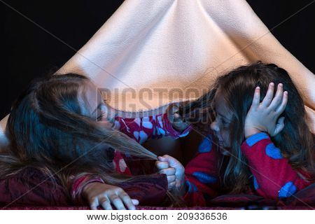 Girl friends under blanket pulling on each others hair. Pyjamas party for children. Children and pyjamas party concept. Kids wearing red jammies in bed on black background.