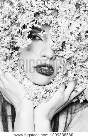 Beautiful girl model in lilac flowers around face with sexy lips on white background